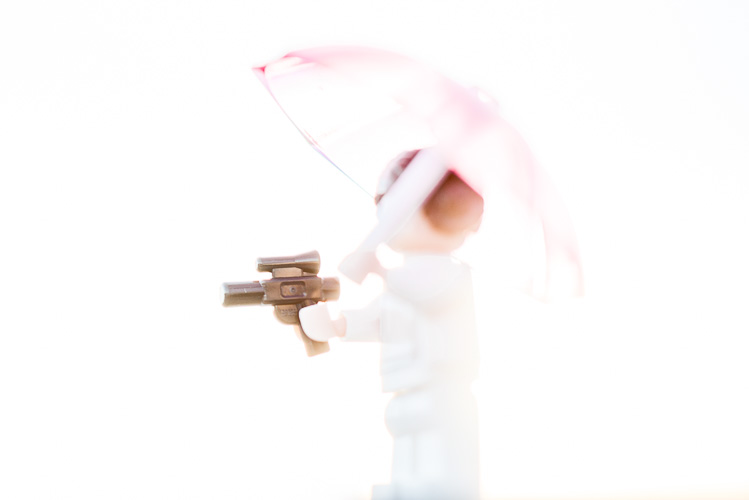A doll with an umbrella and a plastic gun